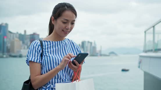Thumbnail for Woman hold with shopping bag and use of mobile phone