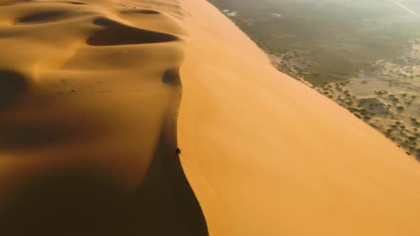 Thumbnail for Aerial view of a man sitting on the edge of dunes, U.A.E.