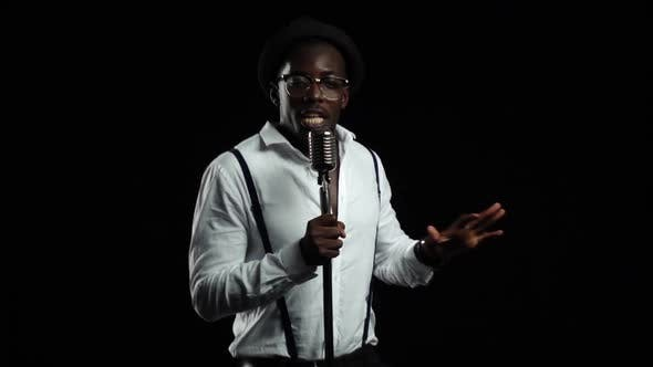 Thumbnail for African American with Glasses Singing and Dancing To the Music From the Microphone. Black Background