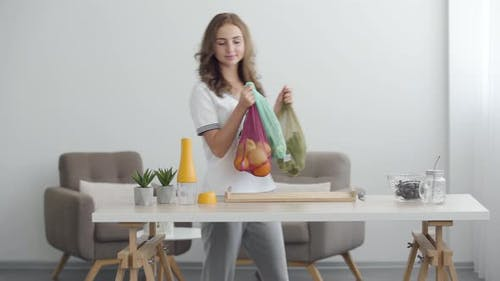 Young Smiling Woman Putting Bags with Fruit and Vegetables on the Table in Modern Office