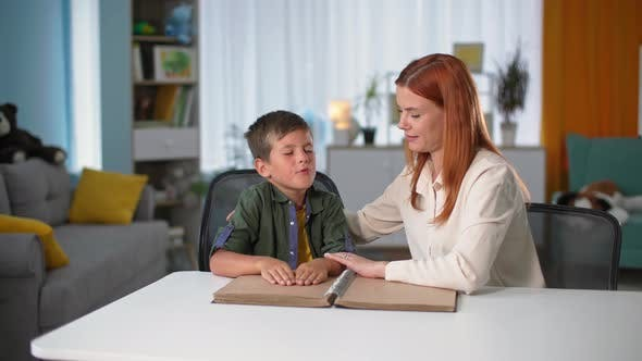 Disabled Kid Learns to Read Braille Female Teacher Helps Blind Boy Move His Fingers Through the Font