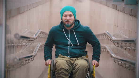 Thumbnail for Disabled Man in Wheelchair Smile and Showing Opportunities of His Wheelchair - Moving on the Sides