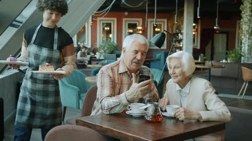 Elderly Couple Using Smartphone and Talking While Waitress Bringing Desserts in Cafe