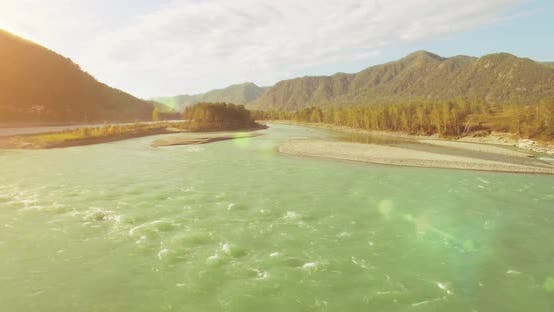 Cover Image for UHD Aerial View. Low Flight Over Fresh Cold Mountain River at Sunny Summer Morning. Green Trees and