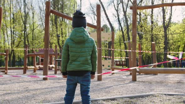Child Standing Near a Closed Playground