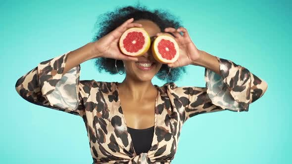 Cover Image for Pretty african american woman in leopard print top dancing with two half of juicy grapefruit