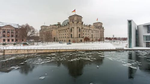 Time lapse of the Reichstag Berlin and spree river in the winter time with snow