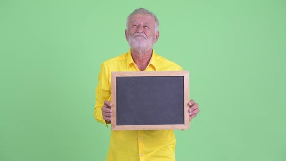 Thumbnail for Happy Senior Bearded Businessman Thinking While Holding Blackboard
