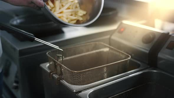 Thumbnail for The Cook Fills the Fryer with Raw Potato for Making Fries in Slow Motion, Making the French Fries