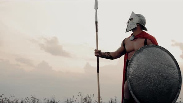 Shirtless Spartan Posing with Spear in Field