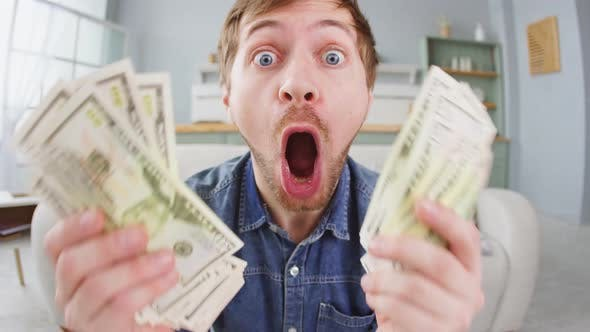 Thumbnail for Portrait of excited young man holding bunch of money banknotes and celebrating