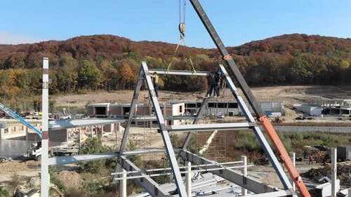 Aerial Shot Installation of a Roof and a Framework From a Metal Construction. Workers Mount the Roof