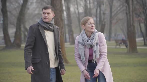 Thumbnail for Portrait of Stressed Caucasian Pet Owners Losing Dog or Cat in Park. Worried Adult Man and Woman