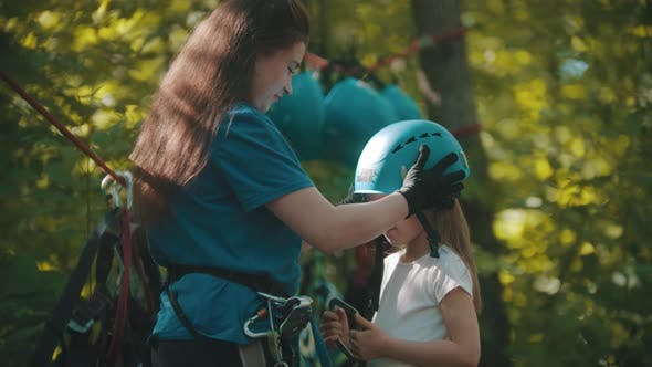 Cover Image for Woman Instructor Putting on a Little Girl Protective Helmet for the Rope Adventure