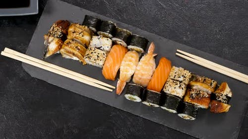 Variety Mix of Traditional Sushi Rolls on Black Stone Plate