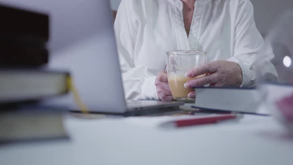 Thumbnail for Close-up of Mature Female Hands Holding Coffee Cup and Using Laptop
