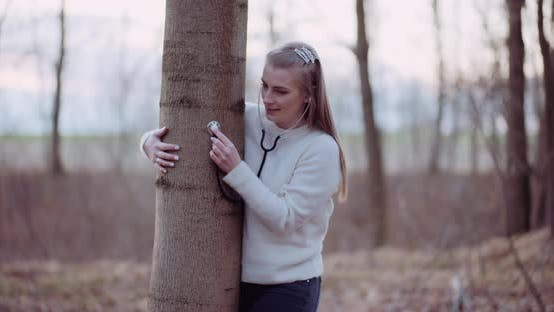 Thumbnail for Woman Uses a Stethoscope and Examines a Tree in the Forest