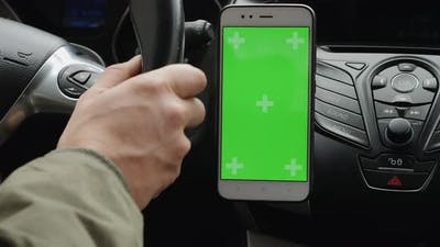 Smartphone with Green Screen on the Dashboard