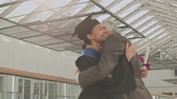 Old University Teacher Congratulating Mixed-race Female Graduate