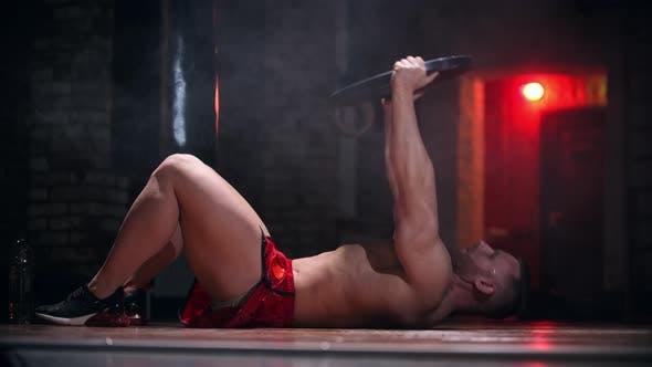 Harter Mann macht Übungen - pumpt seine Bauchmuskeln und hält eine Metallscheibe als das Gewicht