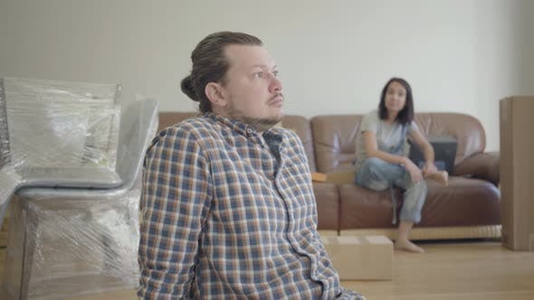 Thumbnail for Sad Caucasian Man Sitting and Looking Away As His Wife or Girlfriend Blaming Him on the Background
