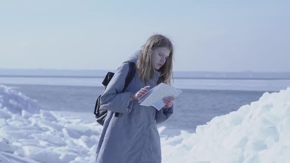 Thumbnail for Young Blond Pretty Woman Wearing Warm Jacket Standing on the Glacier Checking with the Map