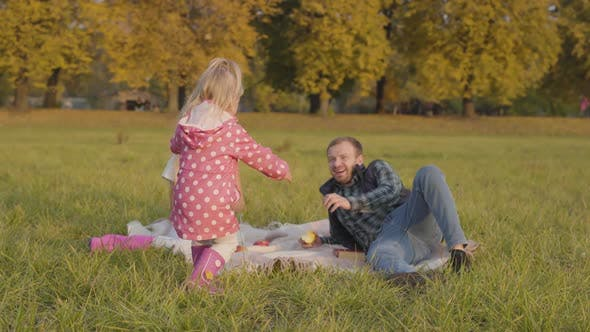 Thumbnail for Little Blonde Child Dressed in Pink Clothes Walking To the Elder Sister and Father Sitting