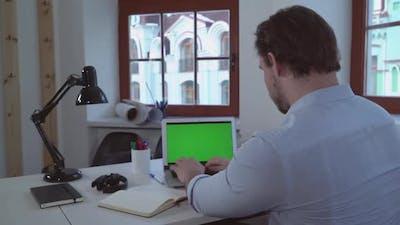 Man Typing on Laptop Green Screen
