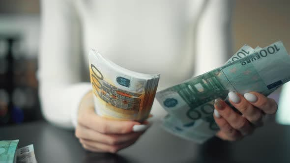 A Woman Is Holding Money and Counting Euro Bills