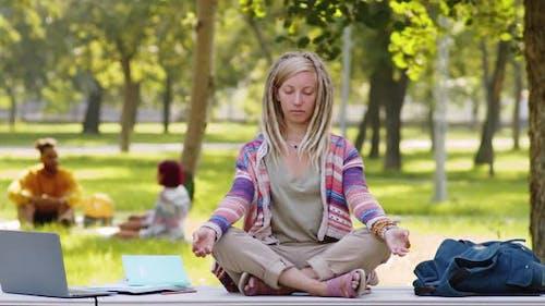 Female College Student Meditating in Lotus Pose in Park