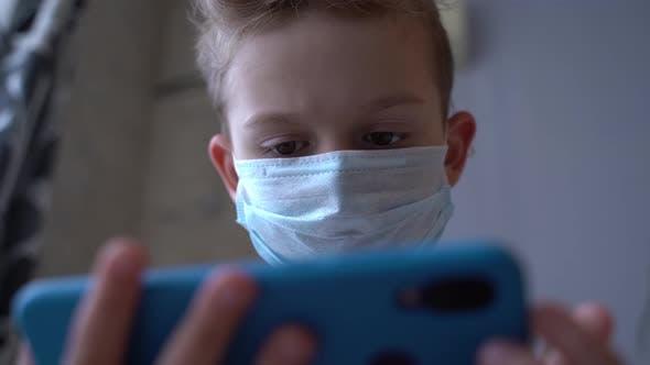 Ein Kind in einer medizinischen Maske schaut auf das Telefon