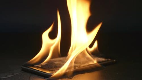 Smashed smartphone is burning on a table