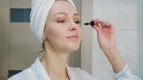 Close Up Shot of Attractive Woman Putting on Makeup with Brush Adding Mascara on Eye and Looks in