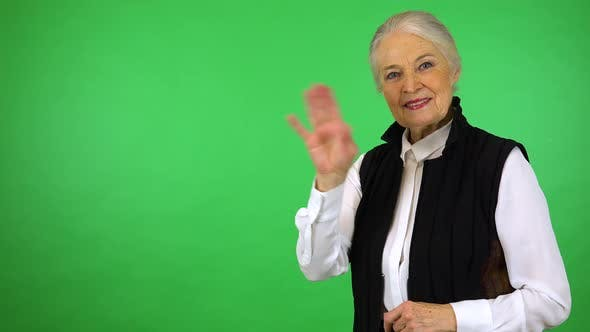 Thumbnail for An elderly woman smiles and waves at the camera - green screen studio
