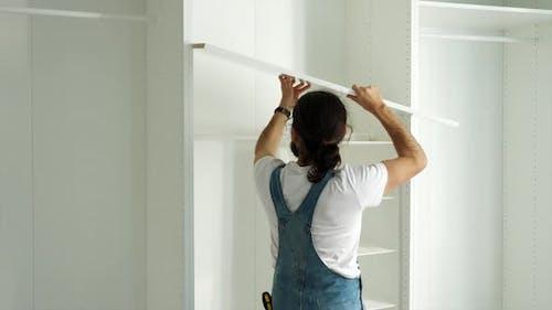 Man Is Installing the Shelf in Wardrobe