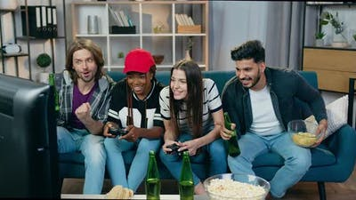 Girls Celebrating Victory in Videogames at Home Together with Male Friends which Watching the Game