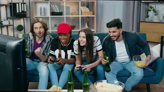 Mädchen feiern Sieg in Videospielen zu Hause zusammen mit männlichen Freunden, die das Spiel ansehen