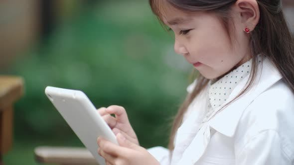 Thumbnail for Adorable Asian Girl Playing on Tablet Outdoors