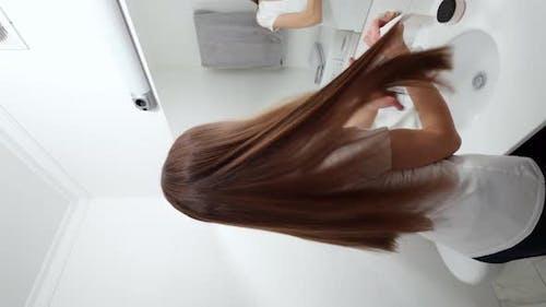Smiling Young Woman Combing Beautiful Long Hair