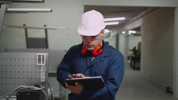 A Male Factory Worker Is Walking on the Workshop Using a Tablet