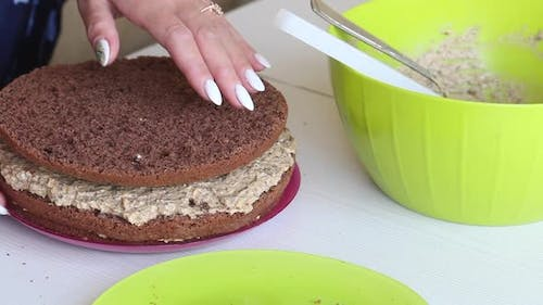 A Woman Is Folding Biscuit Cakes, Smeared With Cream.