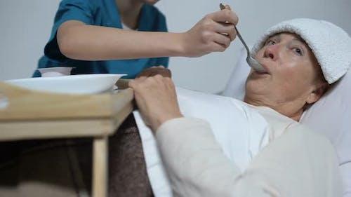 Nurse of Mental Hospital Feeding Indifferent Woman With Porridge, Asylum