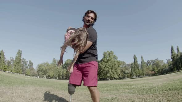 Happy Father with Prosthetic Leg Circling Daughter on Hands
