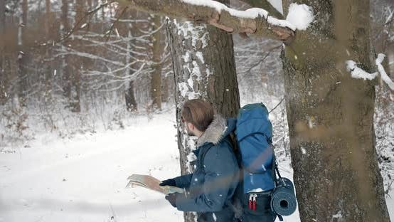 Thumbnail for Man Standing in Forest During Snowfall and Looking at Map