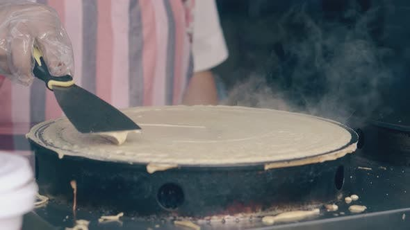 Woman Prepares Pancake on Crepe Maker in Fast Food Cafe