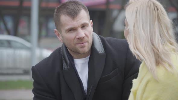 Elegant Caucasian Man Talking To Beautiful Blond Woman and Smiling