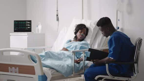 A Young AfricanAmerican Male Doctor is Talking to a Patient