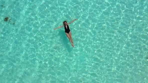 Thumbnail for Beautiful Woman in Black Bikini Is Swimming in the Transparent, Azure Sea. Aerial View of Slim Woman