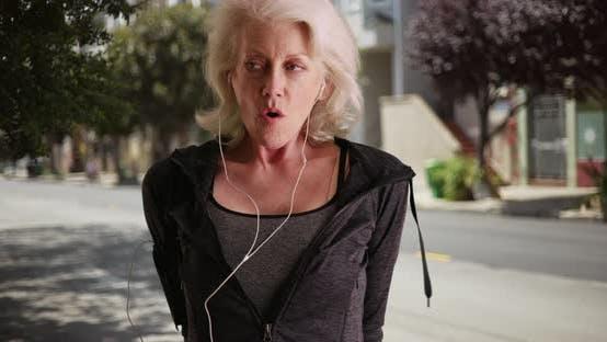 Reifen Frau in Ihr Ende 50s Stretching Ihr Muskeln immer bereit zu joggen außerhalb