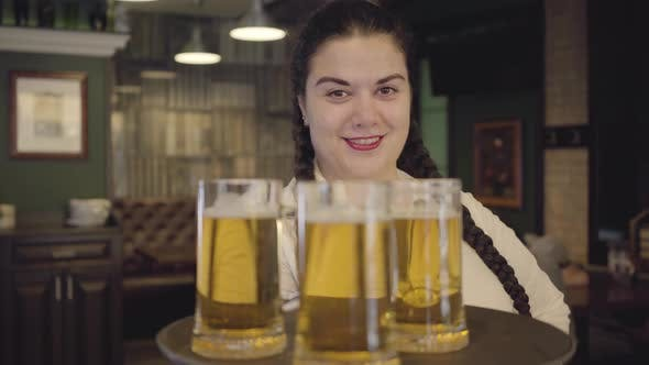 Thumbnail for Portrait Plump Woman with Pigtails in White Blouse Holding Tray with Three Beer Glasses Smiling